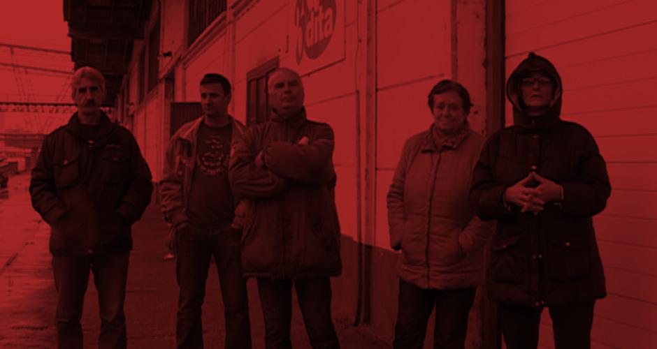 Fünf Dita Arbeiter_innen vor der Fabrik, die sie bewachen, damit die Maschinen nicht abtransportiert werden