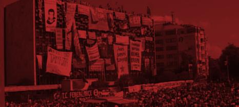 Mit Bannern vollgehängtes großes Gebäude am Taksim Platz in Istanbul, Mensvhen stehtn auf dem Dach, im Vordergrund eine dichte Menschenmasse