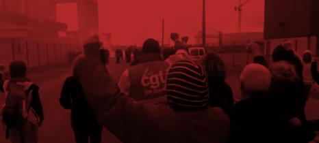 Eien Gruppe von Menschen, teilweise mit weißem Haar mit erhobenen Fäusten von hinten aufgenommen in einer Raffinerie, vor ihnen im Bildhintergund Polizei und Tränengas