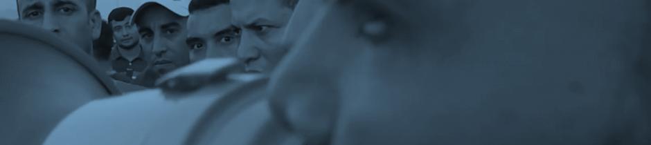 Mann mit Megafon, im Hintergrund Streikende