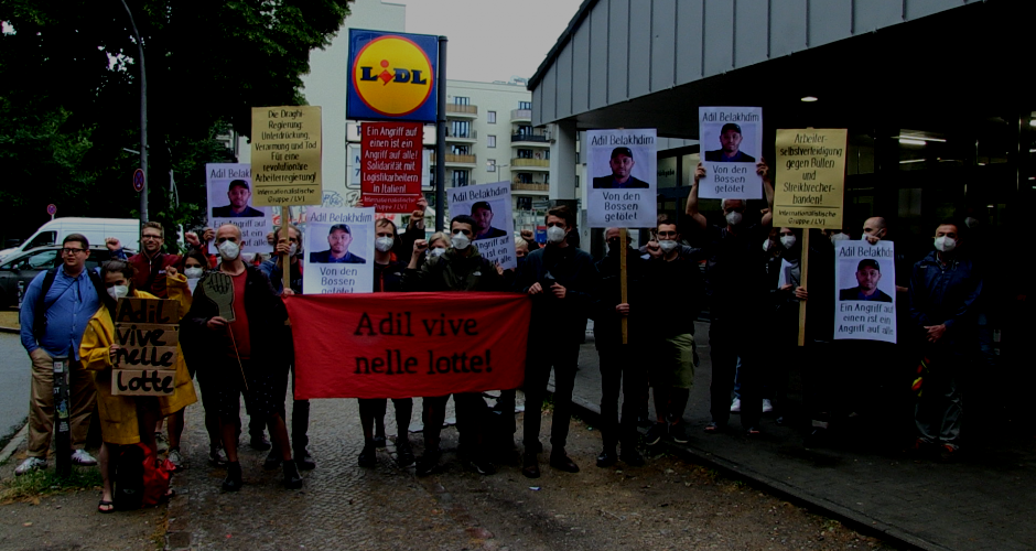 20 Menschen vor Lidl in Berlin mit Protestplakaten