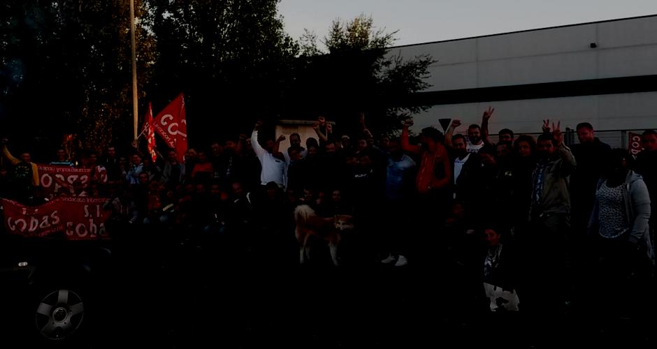 streikende H&M Arbeiter_innen stehen vor ihrem Warenlager in Casalpusterlegno, Lombardei, SICobas Fahnen und erhobene Fäuste
