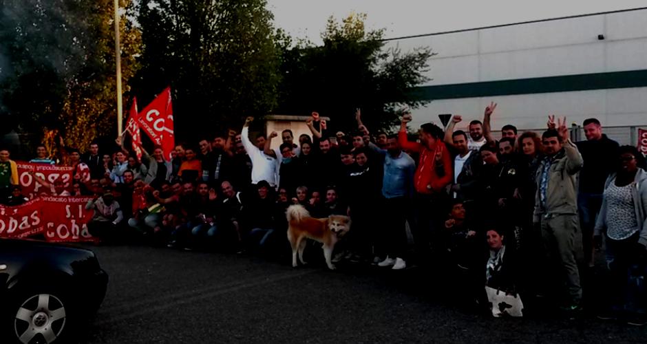 Etwa 70 streikende H&M Arbeiter_innen stehen vor ihrem Warenlager in Casapusterlegno, Lombardei, SICobas Fahnen und erhobenen Fäusten
