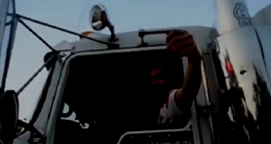 Glücklicher LKW Fahrer spricht durch das Fenster von seinem LKW aus