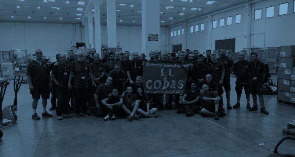 60 GLS Arbeiter_innen halten eine SI Cobas Fahne mit Trauerflor