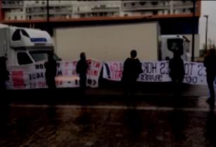 sieben Personen halten große Transparente und blockieren die Zufahrt von LKW