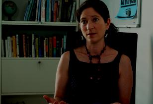 Prof. Julia Steinberger sitzt in ihrem Büro in Lausanne und gibt labournet.tv ein Interview