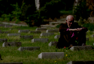 Sohn eines der in Treuenbrietzen von der Wehrmacht ermordeten Italienischen Kriegsinternierten sitzt auf dem Friedhof vor dem Grab seines Vaters