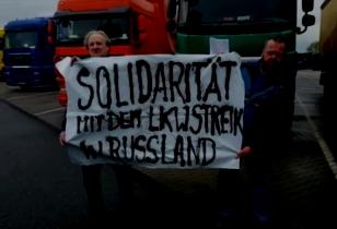 """Zwei Trucker stehen auf einem LKW Parkplatz und halten ein Transparent mit der Aufschrift: """"Solidarität mit dem LKW Streik in Russland"""""""
